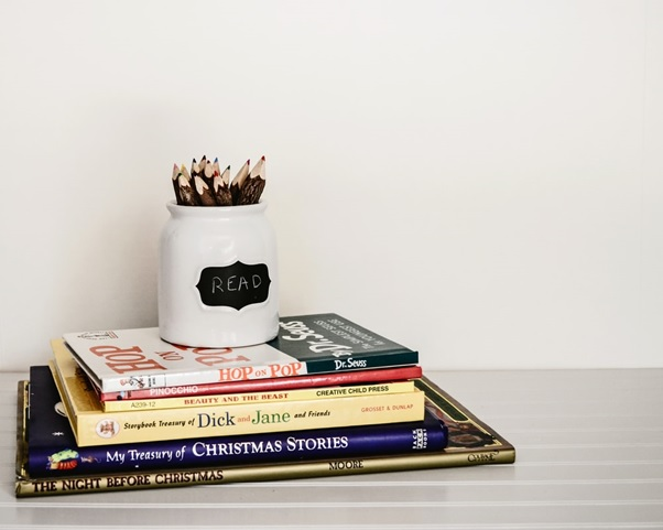 A pile of books with a collection of pencils on top