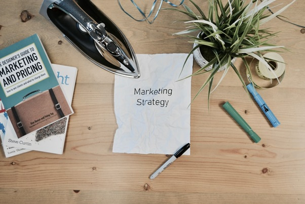 'Marketing Strategy' Typed on a Creased Page and a Flat Iron Smoothing It Over